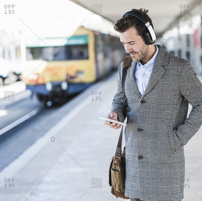 Young businessman with cell phone and headphones at the train station