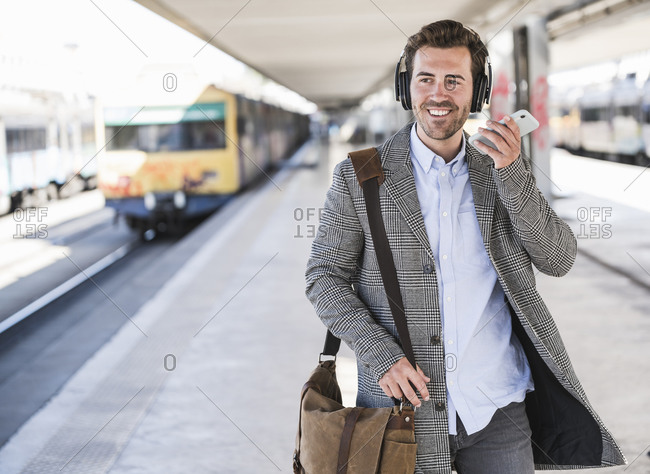 Smiling young businessman with cell phone and headphones at the train station