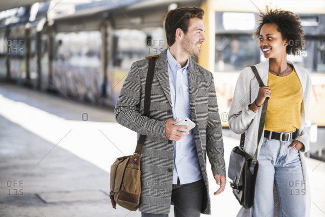 Happy young businessman and businesswoman walking and talking at the train station