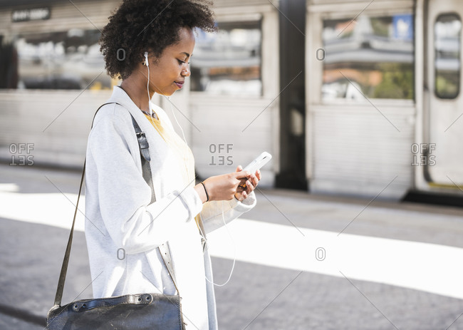 Young woman with cell phone and earphones at the train station