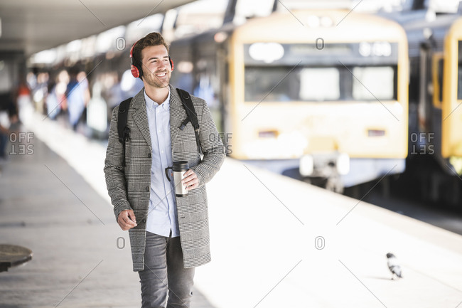 Young businessman with coffee mug and headphones at the train station