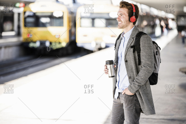 Smiling young businessman with coffee mug and headphones at the train station
