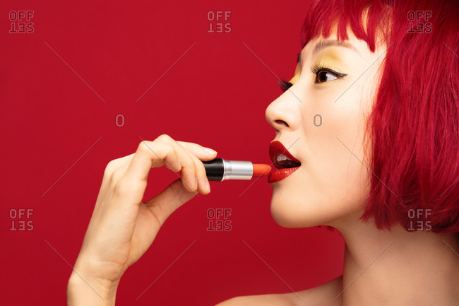 Young woman with short red hair puts on red lipstick