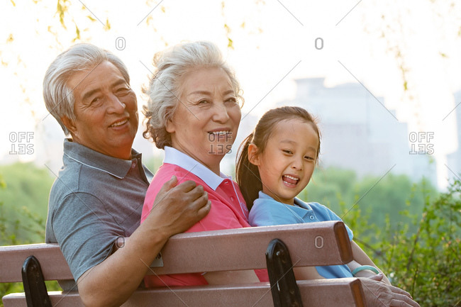The elderly couple in the park with a granddaughter