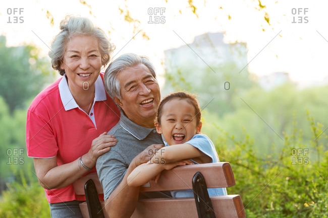 Elderly couple in the park with a granddaughter
