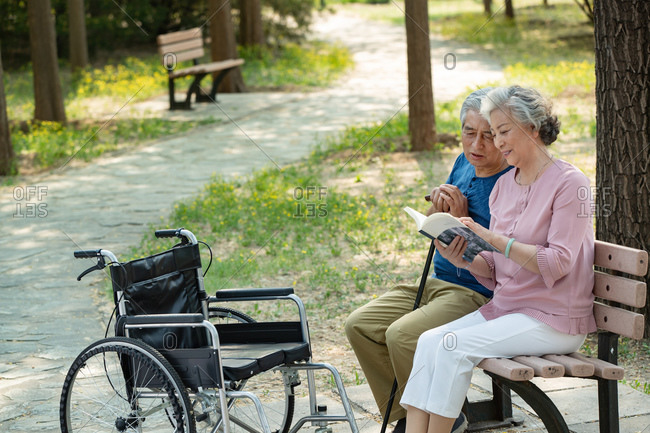 Elderly couple sitting in the park reading a book