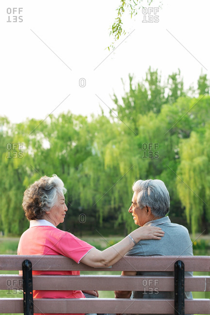 Happy elderly couple sits on a bench together