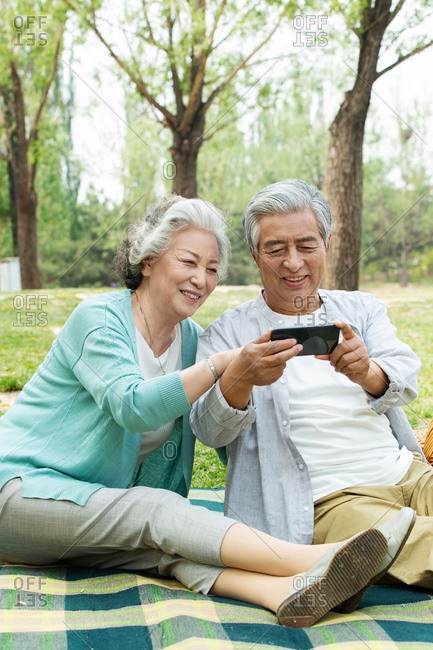 Elderly couple watch mobile phone