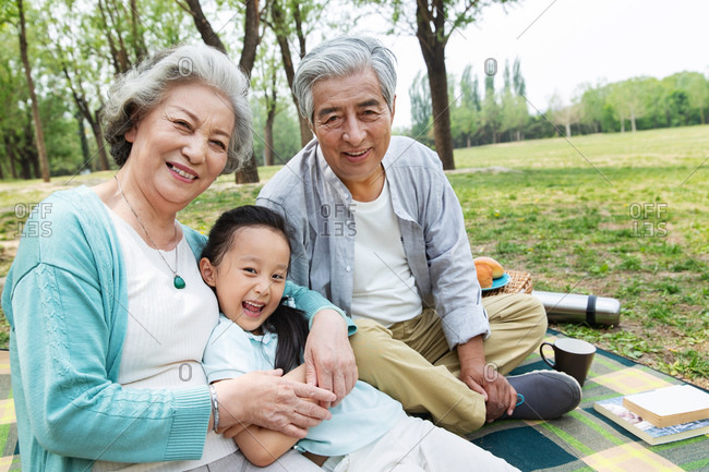 Elderly couple having a picnic in the park with their granddaughter