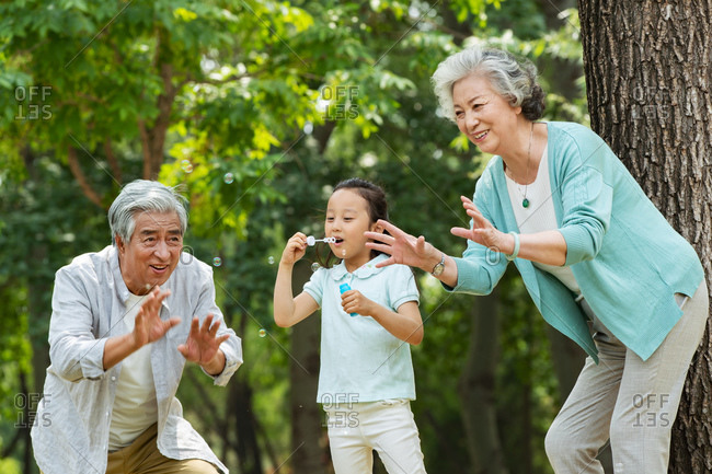 Elderly couple and granddaughter blow bubbles