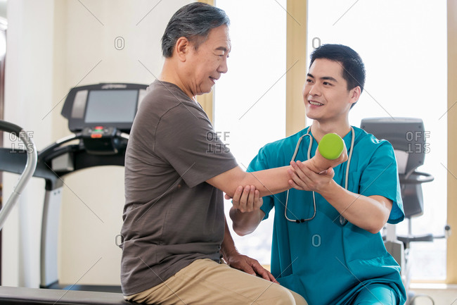 The doctor helps the patient do his rehabilitation exercise