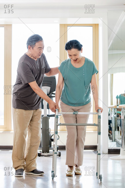 Elderly man helps his wife do her rehabilitation exercise