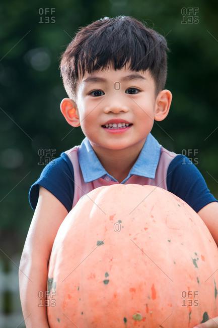 Asian boy holds a pumpkin
