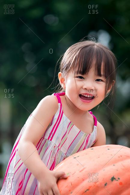 Asian girl holds a pumpkin