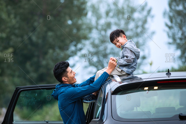 Father holds son as he sits on the roof of the car