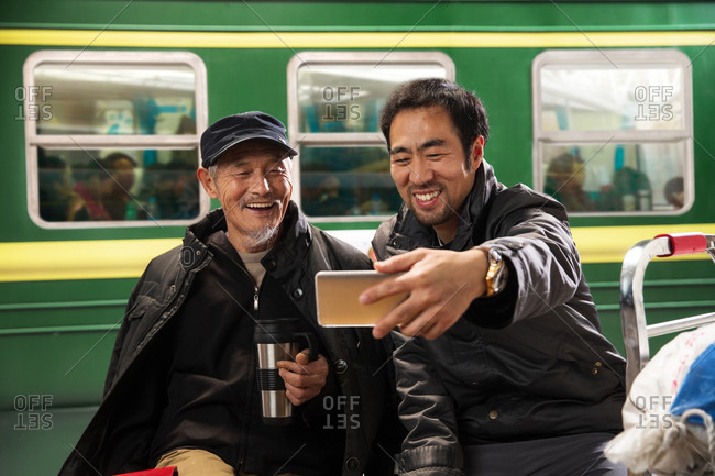 Two men take a selfie at the train station