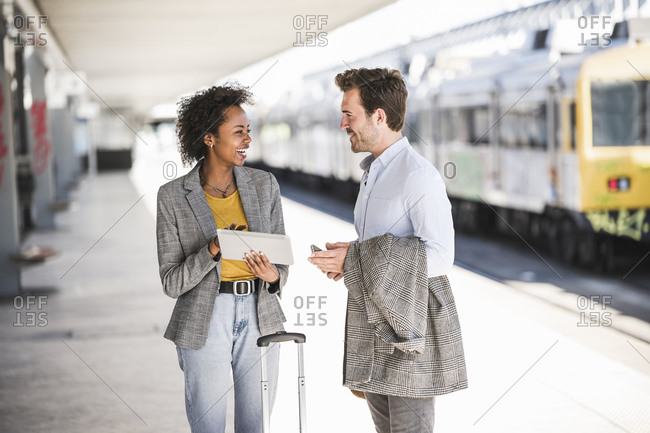 Young businessman and happy businesswoman using tablet together at the train station