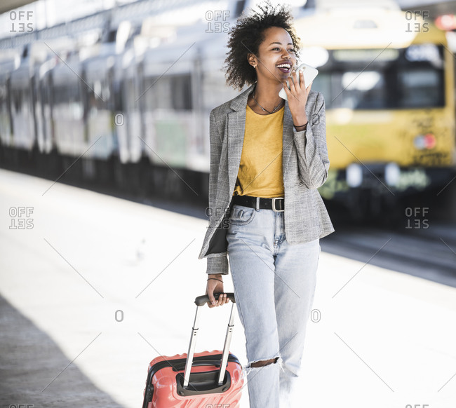 Happy young woman using cell phone at the train station
