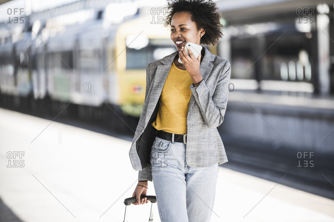 Smiling young woman using cell phone at the train station