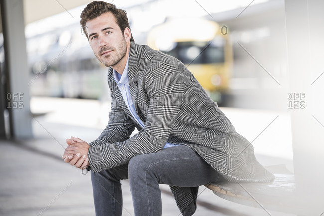 Portrait of young businessman sitting at the train station