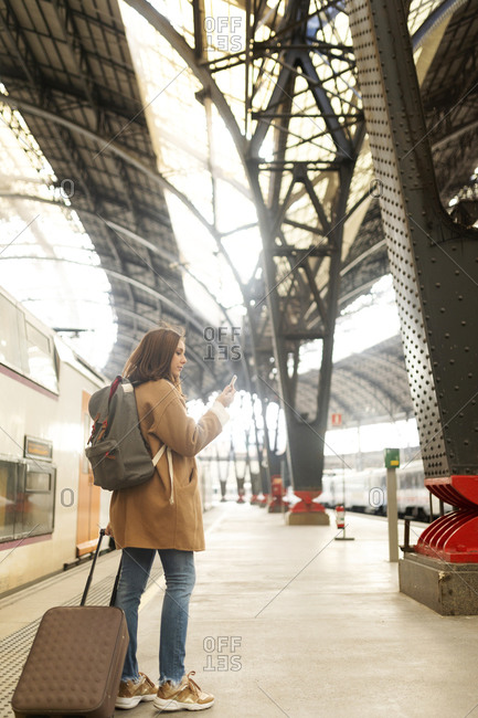 Young woman using cell phone at the train station