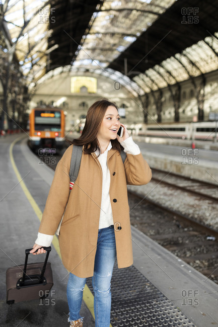 Young woman talking on the phone at the train station