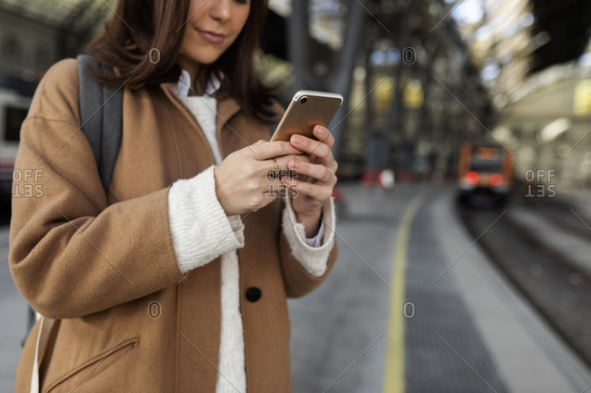 Close-up of woman using cell phone at the train station
