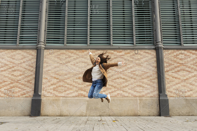 Excited young woman jumping in the city