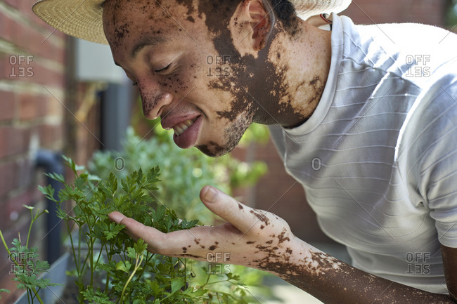 Young man with vitiligo with a hat smelling the plants