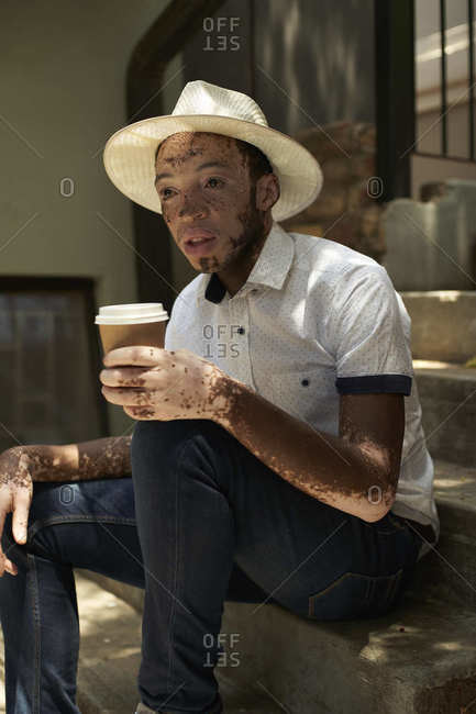 Portrait of young man with vitiligo wearing a hat- holding a takeaway coffee sitting on the stairs