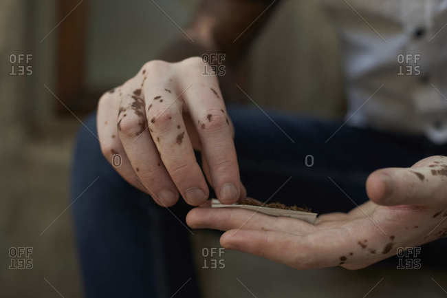 Close-up of young man with vitiligo rolling a cigarette