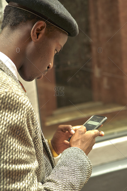 Stylish businessman wearing a beret checking his smartphone