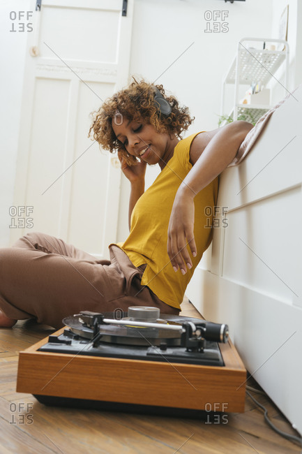 Young woman listening to music with headphones and record player at home