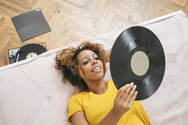 Young woman lying on bed listening to music with headphones and record player