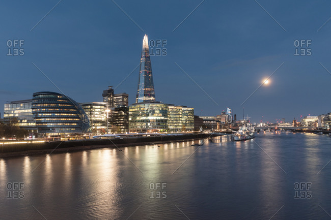 UK- England- London- River Thames and illuminated waterfront skyscrapers at early dawn