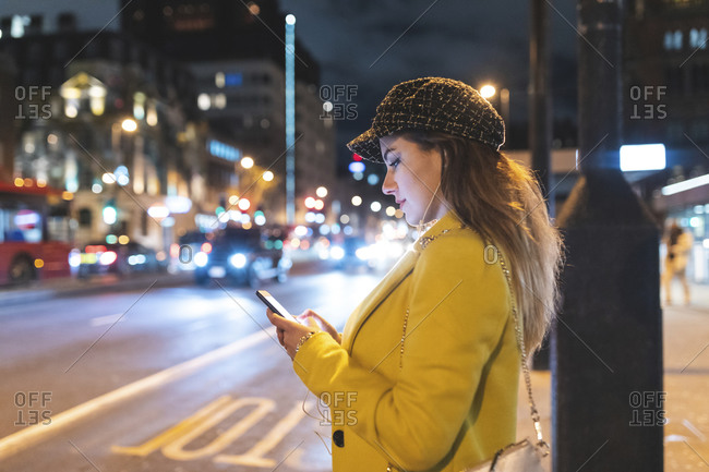Woman with her smartphone in the city at night next to a road in London- Great Britain