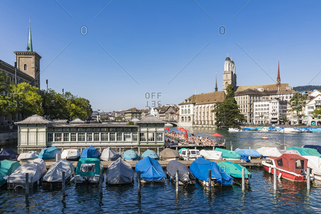August 24, 2019: Switzerland- Canton of Zurich- Zurich- Boats moored on Limmat river with swimming pool in background