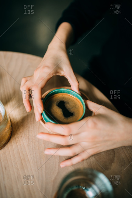 Hands of a woman drinking espresso in a cafe