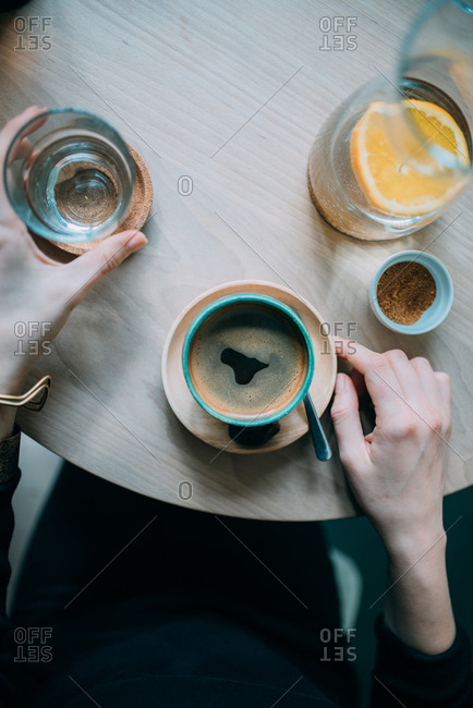 Overhead view a woman drinking espresso and lemon water in a cafe