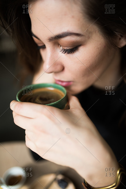 Close up of woman sipping an espresso