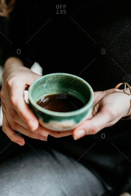 Hands of a woman holding espresso
