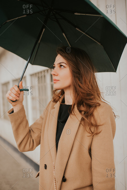 Beautiful brunette woman standing outside with umbrella