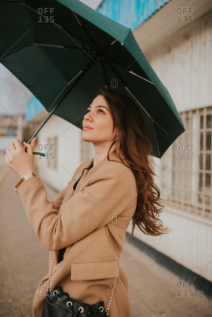 Side view of a beautiful brunette woman standing outside with umbrella
