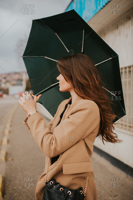 Young brunette woman looking away while standing outside with umbrella
