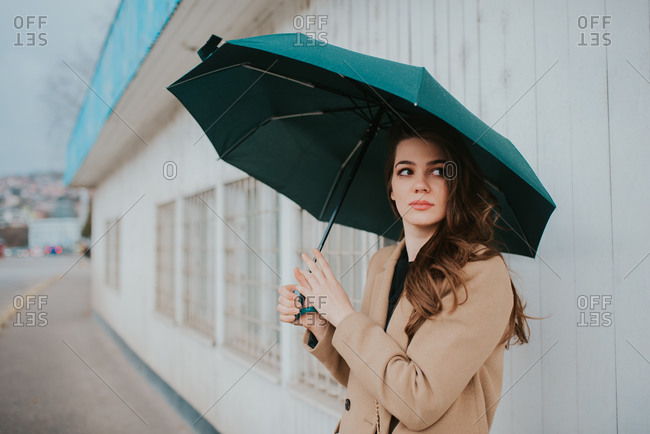 Brunette woman standing outside with umbrella
