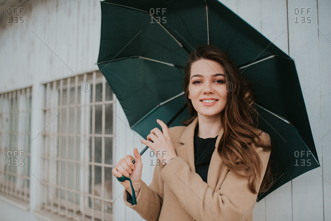 Portrait of a smiling brunette woman standing outside with umbrella