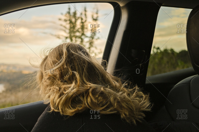 Rear view of blonde woman looking out window while riding in car