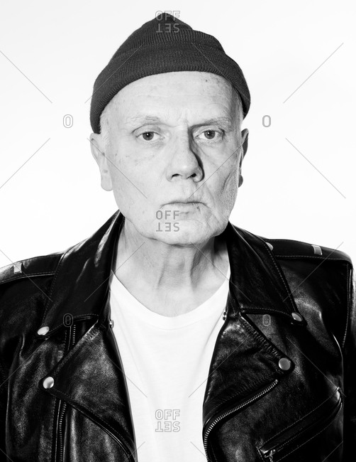 Senior man wearing leather jacket and knit hat looking at camera in black and white