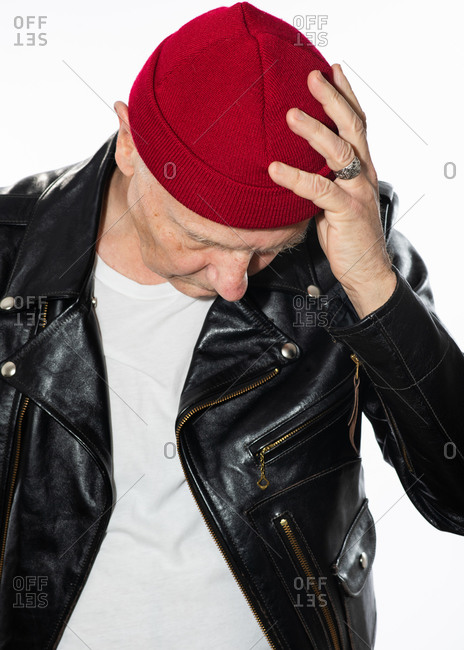 Senior man wearing leather jacket and a red knit hat looking down