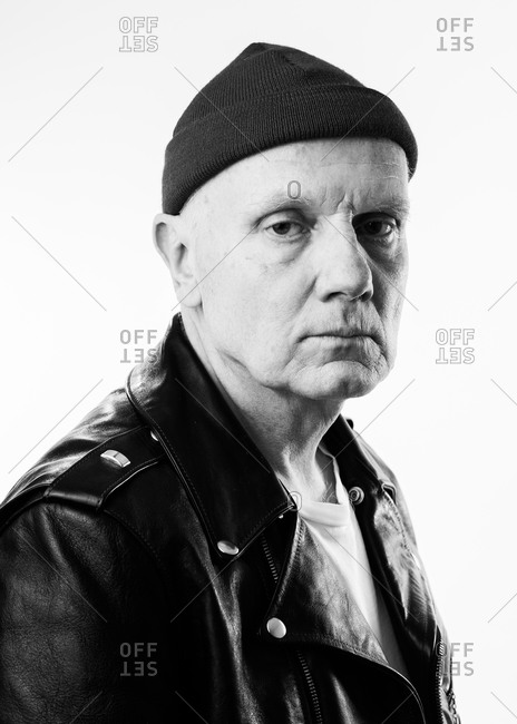 Older man wearing leather jacket and knit hat looking at camera in black and white